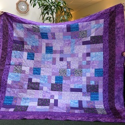 Beautiful hand crafted Double quilt in a selection of mauves and purples, with a cotton wadding and an auborgine coloured backing.