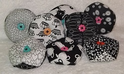 Black and white pin cushions with a coloured button centre. A random design will be sent.