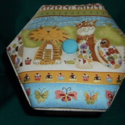Approx 5.5inches across X 4.5inches high. Contains folding scissors, buttons, threads, pins, tape measure, needles and more. Sides drop down to display contents. Gently pull ribbons to reassemble.