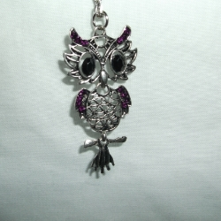 White metal quirky owl with large black eyes and deep purple sparkly stones. Owl is in 3 sections.
