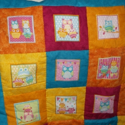 100% cotton fabric, owl quilt in blues, pinks, oranges and yellow with a polyester wadding. Hand quilted. Size 36inches wide x 44 inches long