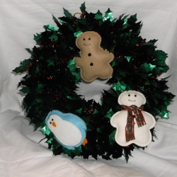 A lovely tinsel wreath with  felt decorations i.e. penguin, gingerbread man and snowman.
