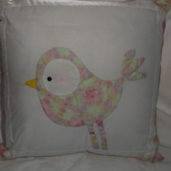 "18"" cushion with cute bird, in a pastel pink and green floral print on a white background. Cushion back is in pink and white stripe with tied envelope cover. The bird has a black bead eye. The cushion is unique."
