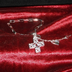 Unusual square filigree cross with padlock and key charms attached with a fine chain. Bracelet measures 7.5 inches in length. 925 silver.